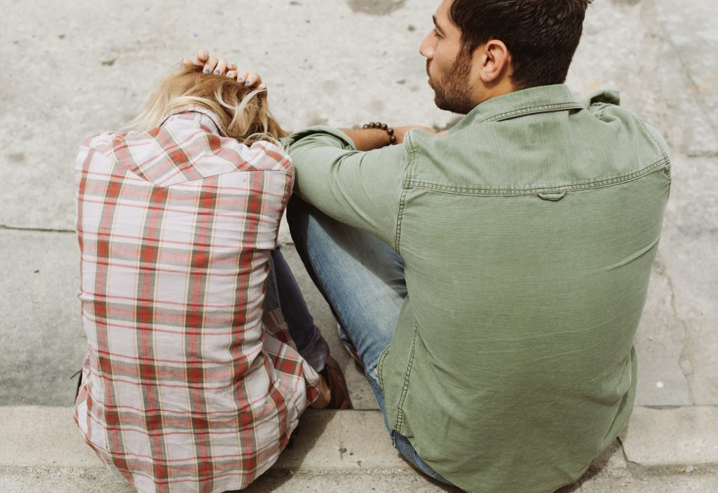 Distressed woman sitting next to disinterested man on sidewalk curb