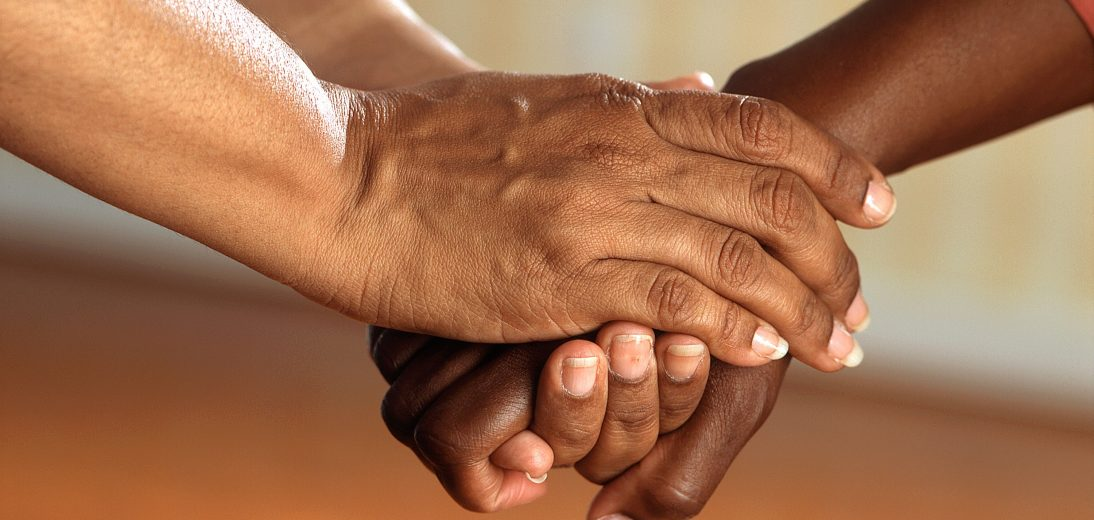 Three women's hands holding each other in support