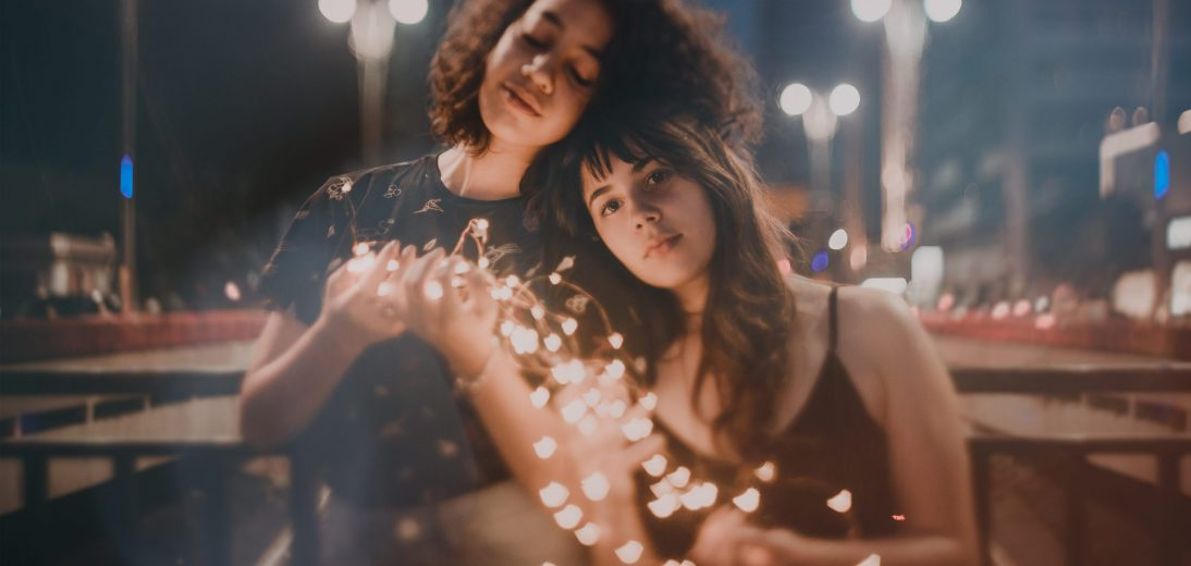 Two women standing close and holding a string of holiday lights