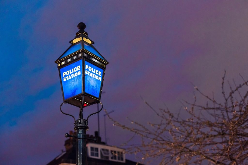 Lampost with blue light that says Police Station