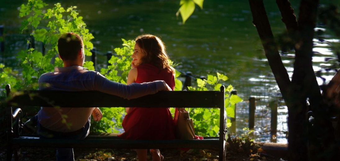 A woman considers a man as they sit on a bench in front of a lake