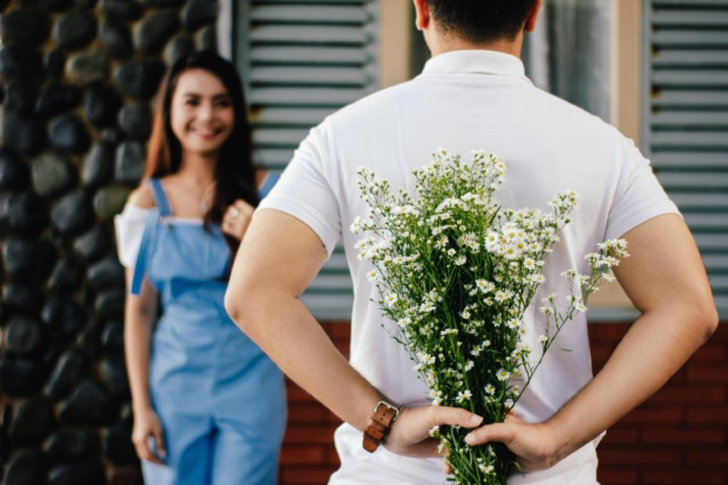 A man holding baby's breath flowers behind his back while a woman looks on