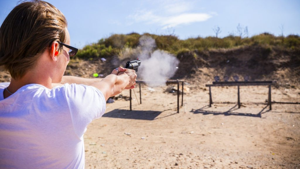 A person firing a gun at a gun range