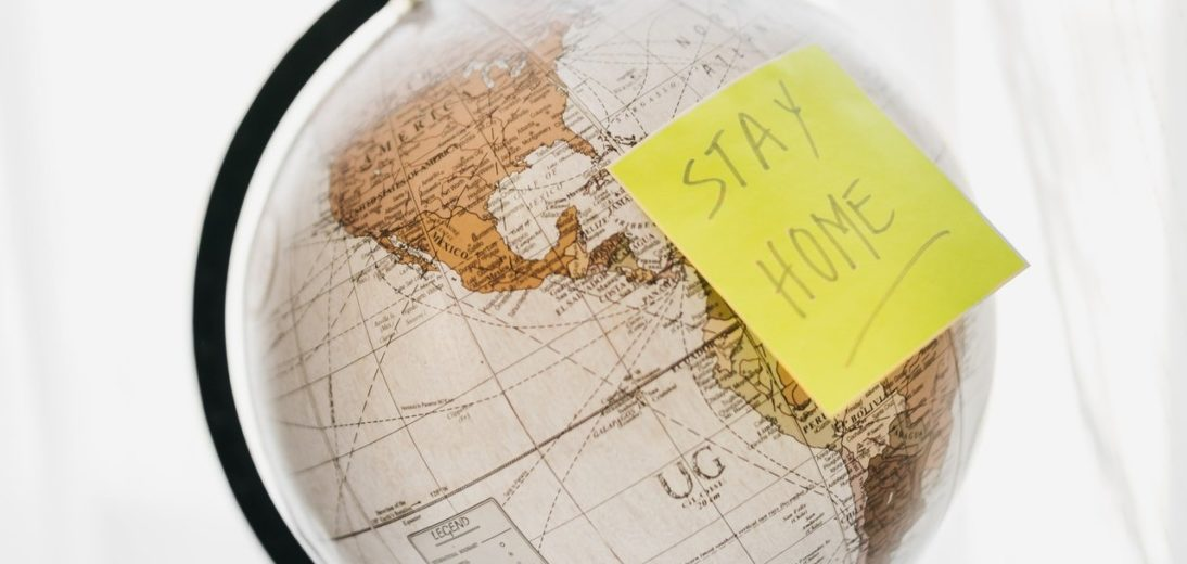 "A globe with a sticky note that says ""stay home"" on it"